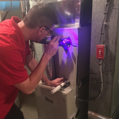 Joe from Attilio checking for a leak in an AC coil with a dye test